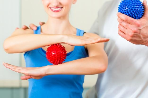 Patientin bei der physiotherapie macht körperliche übungen mit ihrem therapeuten, sie benutzen einen massageball