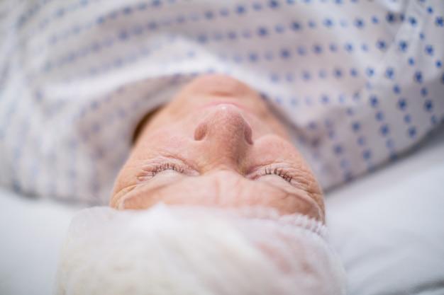 Patientin der älteren frau, die auf bett schläft