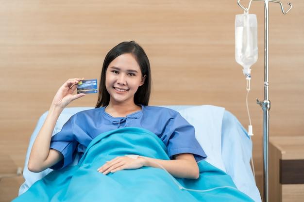 Patientin der jungen frau, die scheingesundheitskreditkarte hält