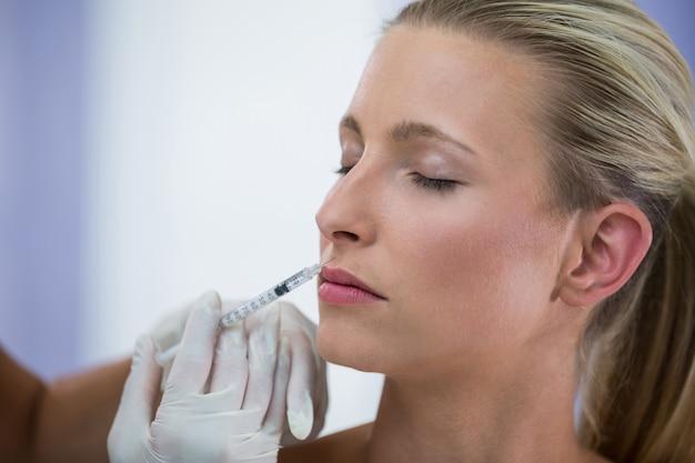 Patientin, die eine botox-injektion im gesicht erhält