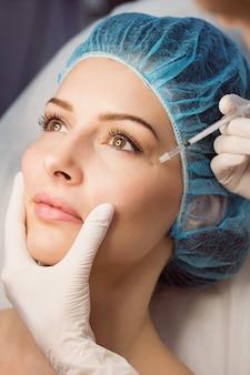 Patientin, die eine injektion auf ihrem gesicht erhält
