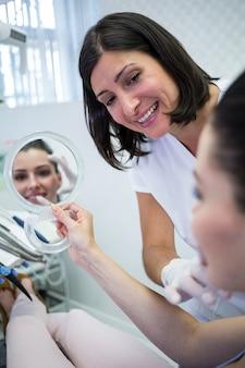 Patientin, die ihr gesicht im spiegel betrachtet
