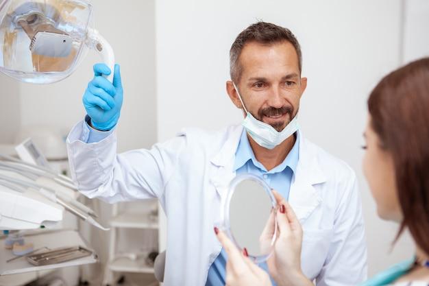 Patientin, die im spiegel nach zahnbehandlung durch professionellen zahnarzt schaut