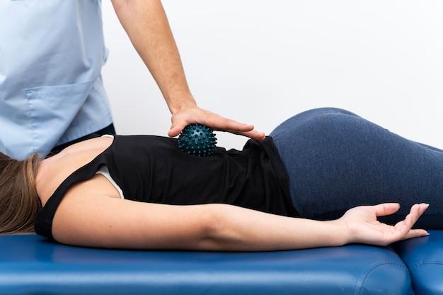 Patientin, die massage vom physiotherapeuten mit ball erhält