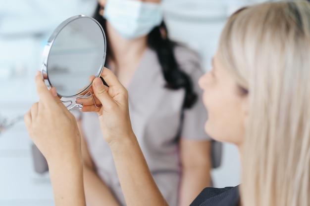 Patientin, die nach der behandlung zu ihrem lächeln im spiegel schaut.