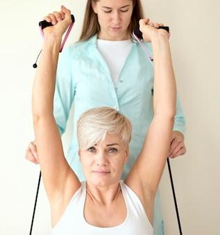 Patientin, die sich einer therapie mit einem physiotherapeuten unterzieht