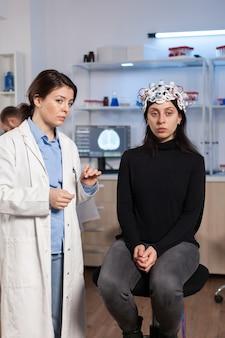 Patientin, die sich in einer neurologischen klinik befindet und ihr gehirn wird gescannt. frau sitzt im labor ausgestattet für die entwicklung von experimenten. neurowissenschaftler auf der suche nach hirntrauma, nervensystem.
