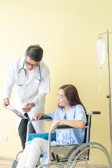 Patientin im rollstuhl mit oberarzt