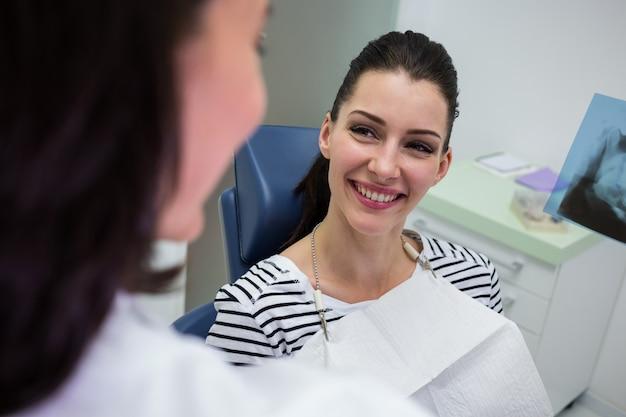 Patientin lächelt, während sie mit dem arzt spricht