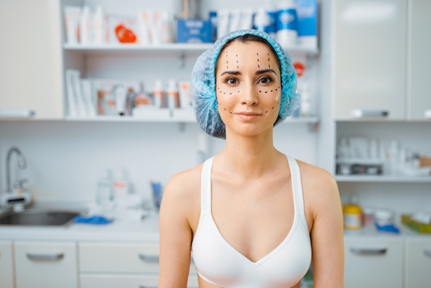 Patientin mit markern im gesicht, büro der kosmetikerin. verjüngungsverfahren im kosmetiksalon. schönheitsoperation gegen falten, vorbereitung auf botox