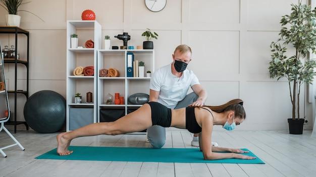 Patientin mit medizinischer maske, die übungen bei physiotherapie mit männlichem physiotherapeuten macht