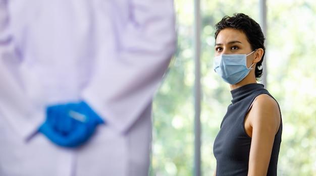 Patientin trägt gesichtsmaske, sitzt verängstigt und hat angst, während der arzt in weißem laborkittel und blauen gummihandschuhen die impfspritzennadel in der hand hinter dem rücken im verschwommenen vordergrund hält und versteckt.