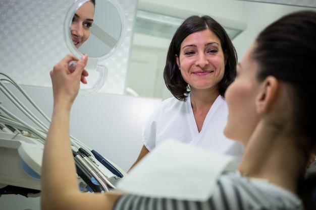 Patientin überprüft ihre zähne im spiegel
