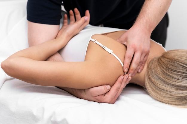 Patientin wird vom physiotherapeuten eine rückenmassage gegeben