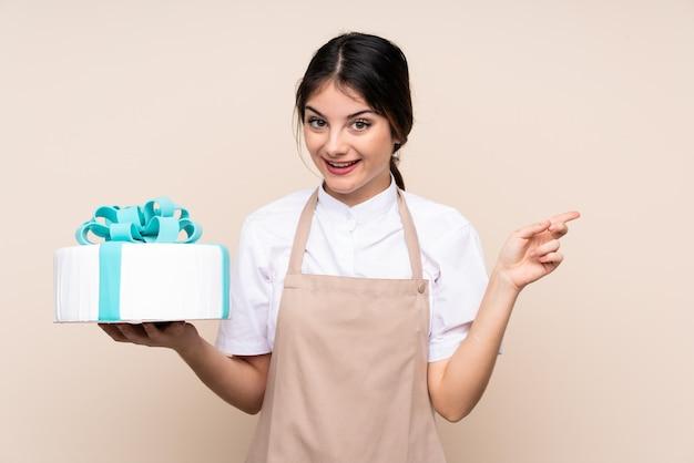 Patissierfrau, die einen großen kuchen über wand überrascht hält und finger auf die seite zeigt