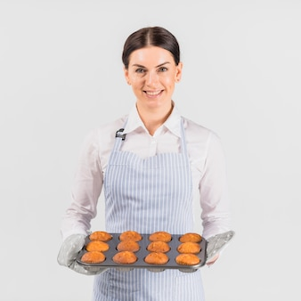 Patissierfrau, die mit muffinzinn lächelt