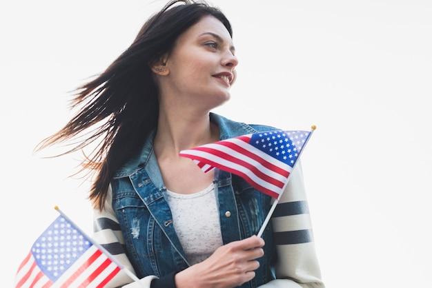Patriotische frau, die flaggen von amerika hält