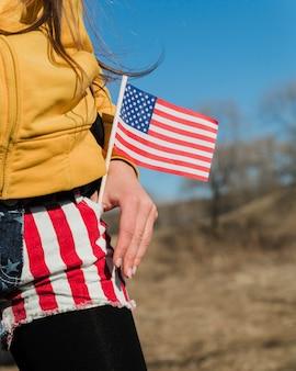 Patriotische frau mit kleiner amerikanischer flagge