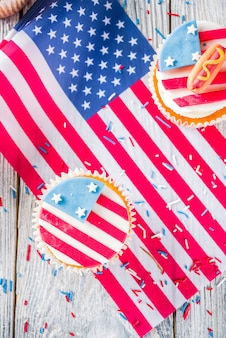 Patriotische usa cupcakes über flaggen auf holztisch