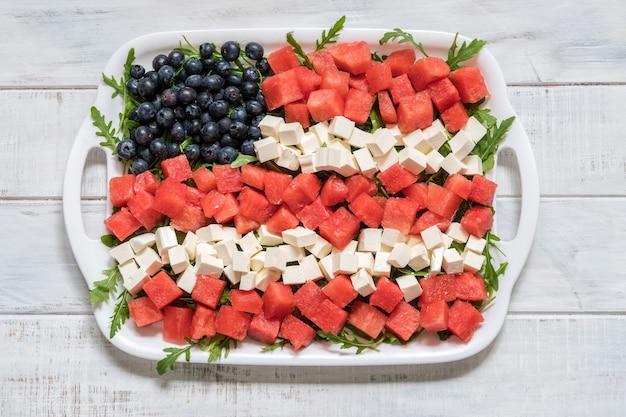 Patriotischer amerikanischer flaggensalat mit blaubeere, wassermelone und feta