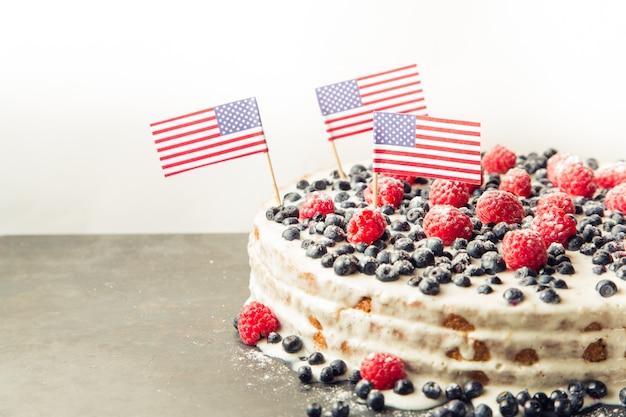 Patriotischer kuchen der amerikanischen flagge mit blaubeeren und erdbeeren auf weinleseweißhintergrund