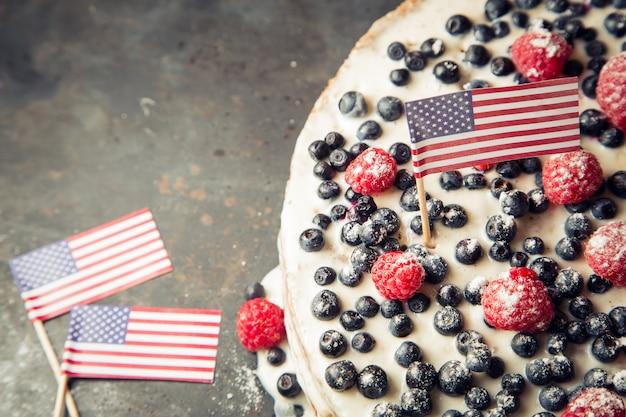 Patriotischer kuchen der amerikanischen flagge mit blaubeeren und erdbeeren
