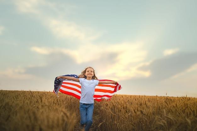 Patriotisches mädchen, das eine amerikanische flagge in einem weizenfeld trägt