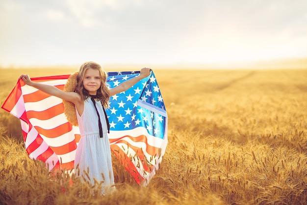 Patriotisches mädchen im weißen kleid, das eine amerikanische flagge in einem weizenfeld trägt