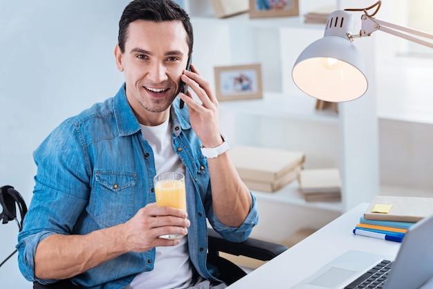 Pause bei der arbeit. fröhlicher invalider, der in seinem rollstuhl sitzt und glas mit saft hält, während er per telefon spricht