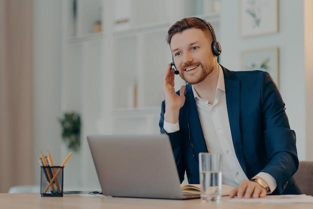 Pause bei der arbeit. froh, dass der männliche unternehmer ein headset auf den ohren trägt und auf dem desktop mit einem laptop-computer posiert, der mit seinen geschäftlichen erfolgen zufrieden ist, hört das webinar online und ruft über die internetanwendung an