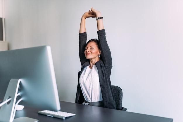 Pause bei der arbeit. weiblicher büroangestellter, der hände ausdehnt.