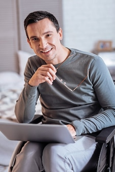 Pause haben. fröhlicher mann, der positivität ausdrückt und laptop auf knien hält