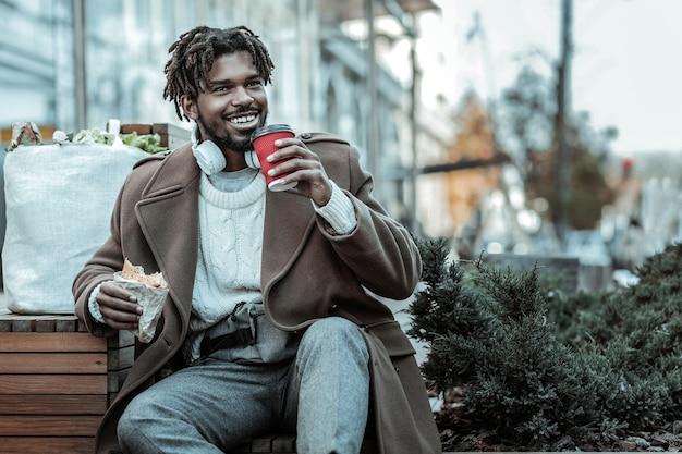 Pause machen. erfreuter brünetter mann, der positivität ausdrückt, während er nach dem gehen auf bank sitzt