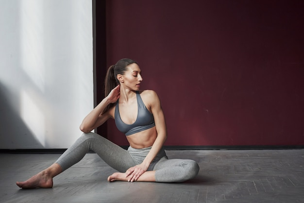 Pause zwischen dem training. hübsche junge frau mit schöner fitnesskörperform sitzt auf dem boden des geräumigen raumes