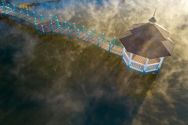 Pavillon auf dem see im morgengrauen, dampfendes wasser von oben