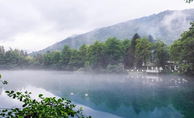 Pavillon zum entspannen am ufer des blauen karstsees cerik-kel bei bewölktem nebelwetter, kabardino-balkar-republik, russland