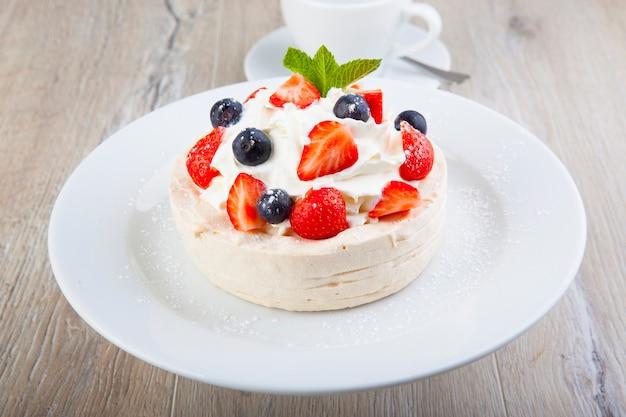 Pavlova-dessert auf einem weißen teller mit einer tasse