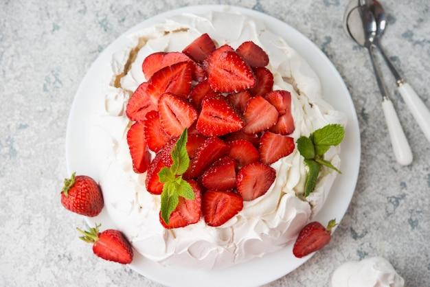 Pavlova-kuchen mit sahne und erdbeeren, selektiver fokus, draufsicht