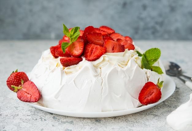 Pavlova-kuchen mit sahne und erdbeeren, selektiver fokus