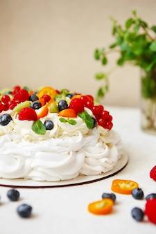 Pavlova-kuchen mit sahne und frischen sommerbeeren