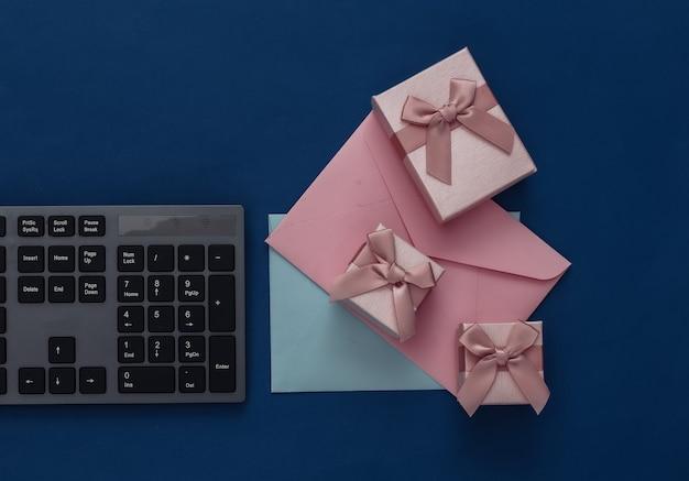 Pc-tastatur, geschenkboxen und umschläge auf klassischem blau.