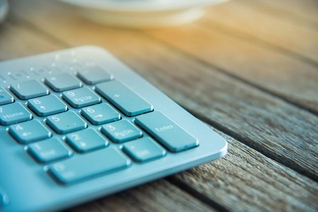 Pc-tastatur und tasse kaffee auf altem verwitterten holztisch
