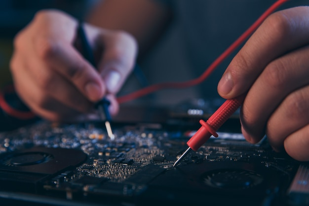 Pc-technologie. computerreparaturwerkstatt. ingenieur, der die laptopwartung durchführt. hardwareentwickler repariert elektronische komponenten.