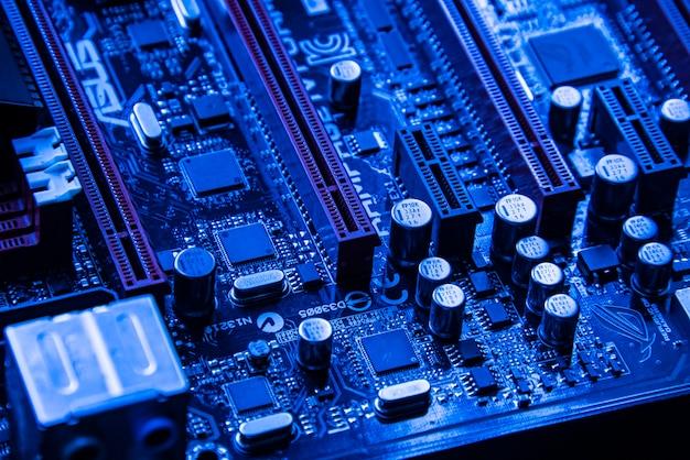 Pci-slot-detail auf dem motherboard eines gaming-pcs in blauem licht