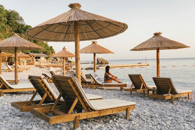 Pebble beach mit hängematten und sonnenschirmen bei sonnenuntergang
