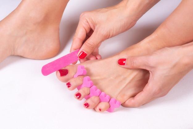 Pediküre auf die füße der frau mit roten zehennägeln auftragen, in rosafarbenen zehentrennern.