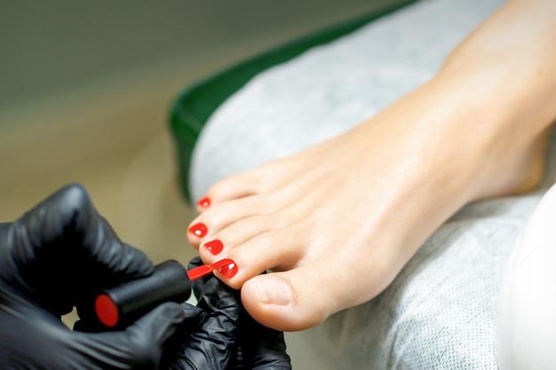 Pediküre-meister, der roten nagellack auf die zehennägel aufträgt