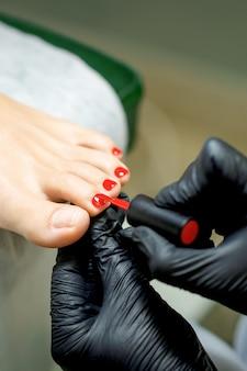 Pediküre-meister, der roten nagellack auf zehennägel der jungen frau im nagelstudio aufträgt