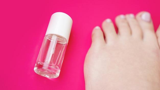 Pediküre mit transparentem nagellack auf rosa hintergrund. gesunde füße, gesundheitsvorsorge