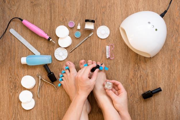 Pediküre zu hause mit nagellack- und uv-lampen, nagelfeilen und scheren. kümmern sie sich bequem von zu hause aus um sich und ihr aussehen. der prozess der farbe nägel.